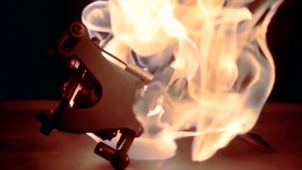 slow motion flames of fire in the dark cover the tattoo machine
