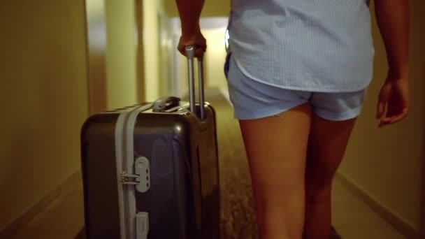 View from behind of a woman carrying luggage across hallway in a luxury hotel, tourism season.