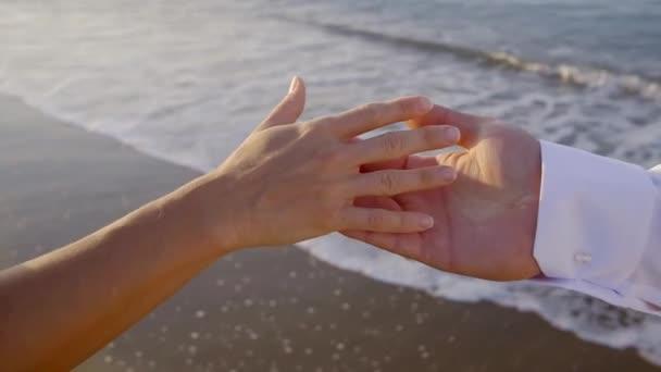 Pár ukazuje lásku prostřednictvím ruka se dotýká na pláži, romantické známky.