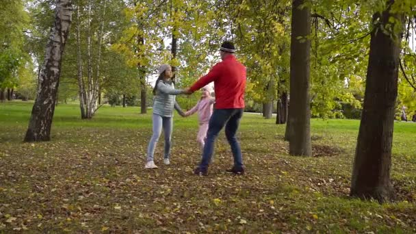 Family of three enjoying fall together in park.
