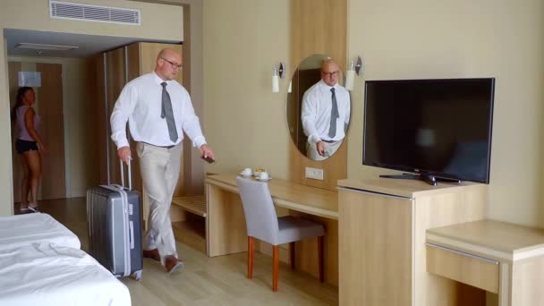 Businessman in a hotel room with a wife, staying in hotel during trip.