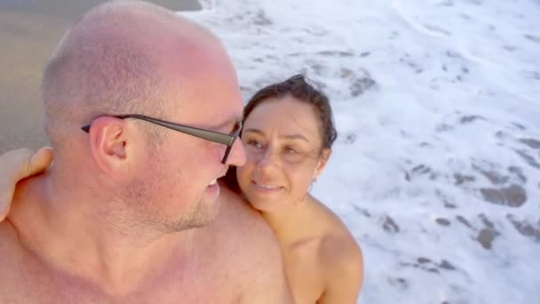 Close-up shot of a cute happy couple kissing on camera on beach.