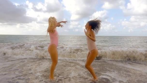 Aktivní dívky tančí na pláži pobřeží v plavky