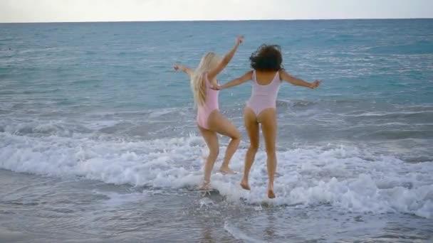Two pretty girls having fun on a beach shore together, splashing.
