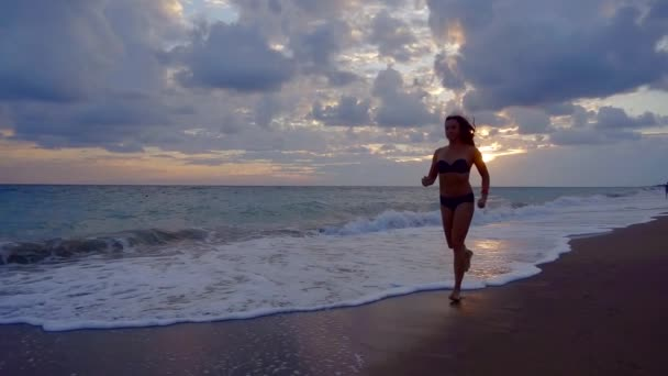 Sexy žena běží podél pláže v pomalém pohybu, večerní natáčení