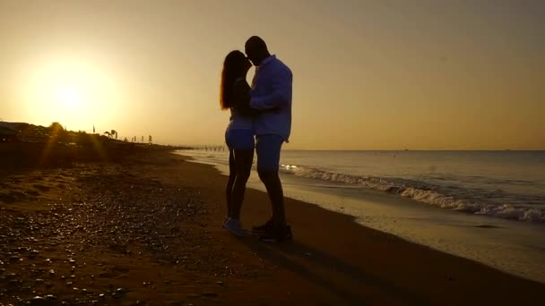 loving couple is standing on a sandy beach near sea in dusk time in summer, man and woman are looking