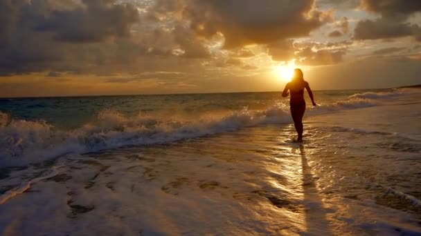 beautiful woman is running on coast of ocean in sunrise time, over tidal waves, amazing beach view