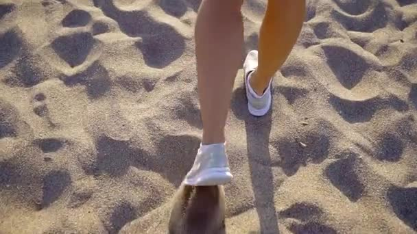 Frau läuft tagsüber im sandigen Boden, Kamera folgt ihr, Blick auf Beine und Turnschuhe