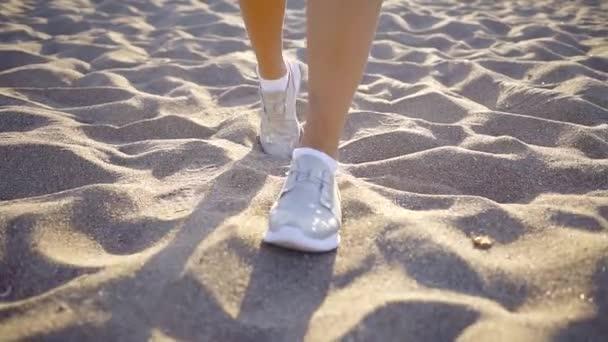 piedi umani sono avviati in luce blu sneakers sportive sono un passo sopra la sabbia in giornata di sole, primo piano