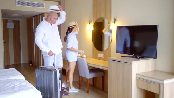 happy married couple is entering with suitcases in hotel room, looking around, smiling and embracing
