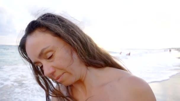 Slow-Motion Blick auf Frau winkt ihr langes dunkles Haar an einem Strand, Nahaufnahme des Kopfes, Porträt