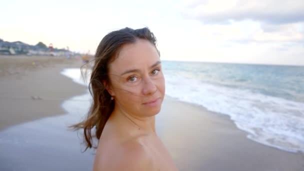 charmante nackte Brünette Frau winkt ihr langes Haar am Meeresstrand, Nahaufnahme von ihrem Gesicht und Schultern