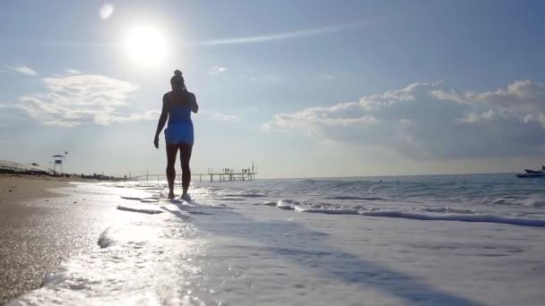 amazing slow motion shot of walking woman on beach with picturesque waves and clouds in sunny day