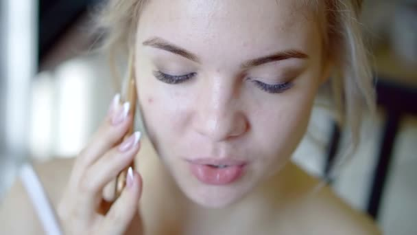 young beautiful blonde girl is talking by mobile phone in a room in daytime, close-up