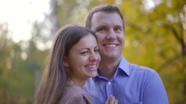 Portrait of a happy smiling couple standing in a park in autumn.
