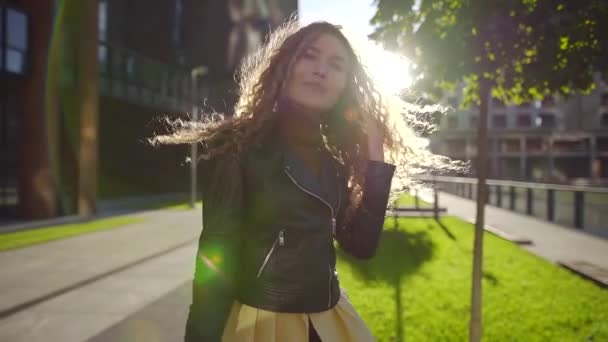 happy trendy woman are dancing on a street against sun in autumn day, looking at camera