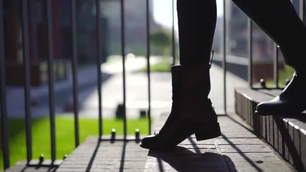 mladá žena je šlápnutí na schodech venku v podzimní slunečný den, pohybující se, detail jejích nohou