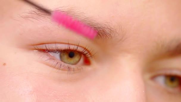 Close-up shot of a cosmetoligist brushing eyebrows.