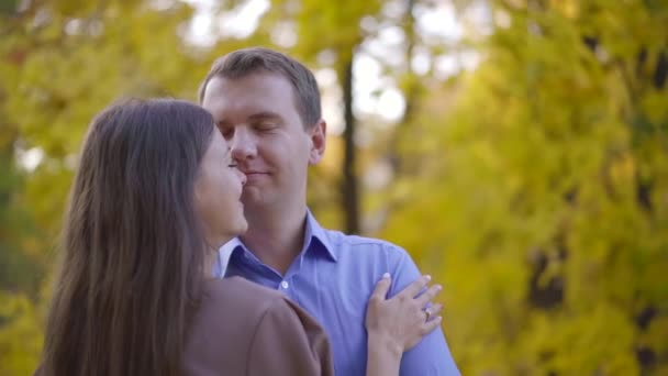 adult funny man is hugging his pretty wife in autumn park, snuggling to her face and bitting nose jokingly