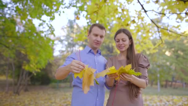 cheerful loving couple is throwing maple leaves in air in daytime in autumn forest, laughing