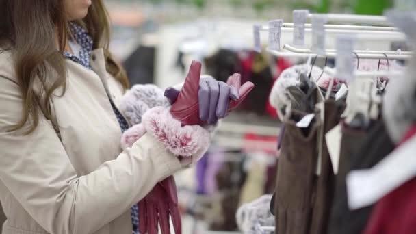 Kundin vergleicht zwei Paar Winterhandschuhe in einem Geschäft, setzen auf verschiedene Hände