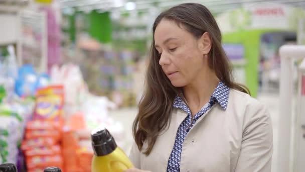 donna brunetta adulta sta leggendo iscrizioni su un etichette su bottiglie con detergente in un corridoio del supermercato