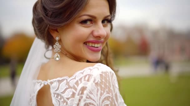Portrét krásné mladé nevěsty ve svatební šaty a závoj s krásnou kytici na podzim Park. Steadicam střílel podél žena
