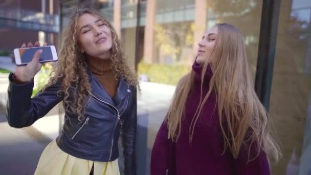 Portrait of a blonde and curly girls dancing together wearing warm clothes in fall.