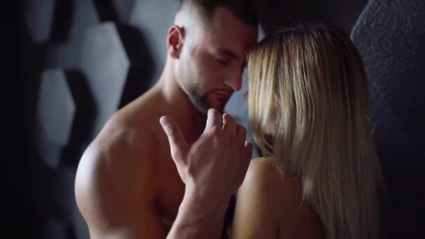 sexy junge athletische Paar umarmt an schwarzer Wand drinnen. ein Mann küsst eine Frau auf die Schulter