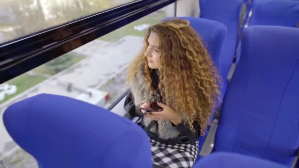 Shot from above of a young girl with smartphone riding on a train and looking out the window.