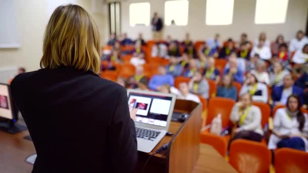 Shot from behind of a businesswoman giving a lecture on a business event, big audience.