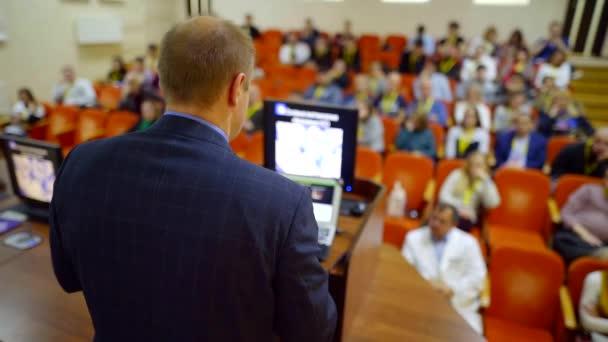 Spezialist auf einem Gebiet, der einen Vortrag auf einer wissenschaftlichen Konferenz hält, Saal voller Fachleute.