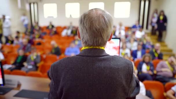 älterer Professor spricht vor Publikum von Wissenschaftlern in Konferenz, die Leute hören zu