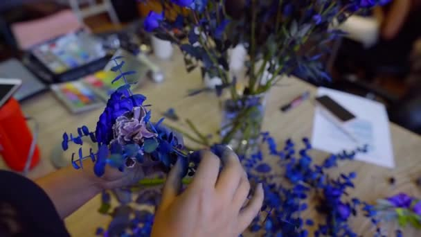 florist is making creative blue bouquet, rotating flowers in hands, painting by blue color, close-up
