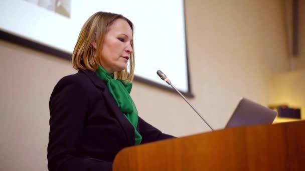 Női üzleti hangszóró a konferencia a színpadon beszélgetés a mikrofont.