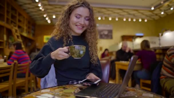 joyful girl is drinking cappuccino in a cafeteria in winter evening, laughing and communicating