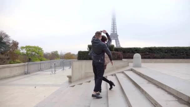 Mann und Frau tanzen und bewegen sich im Freien über eine Treppe in der Stadt, im Hintergrund der Eiffelturm