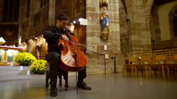 Musiker spielt Cello in der Kathedrale. klassisches Saiteninstrument