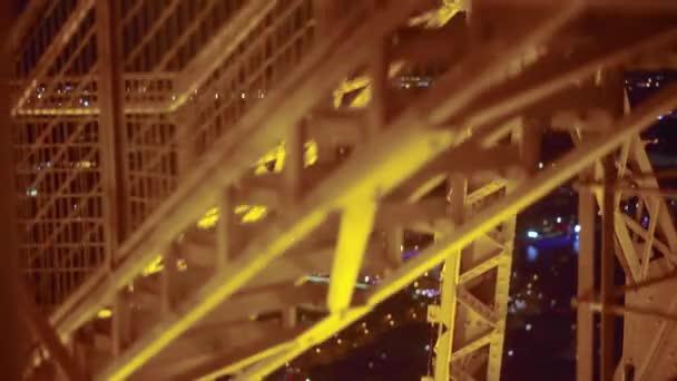 Střelba zářící stavby Eiffelova věž v noci při vstupování na výtah.