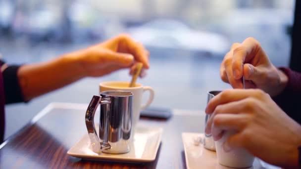 Detailní záběr pár s kávu v kavárně, sedí u okna s pohledem na ulicích Paříže