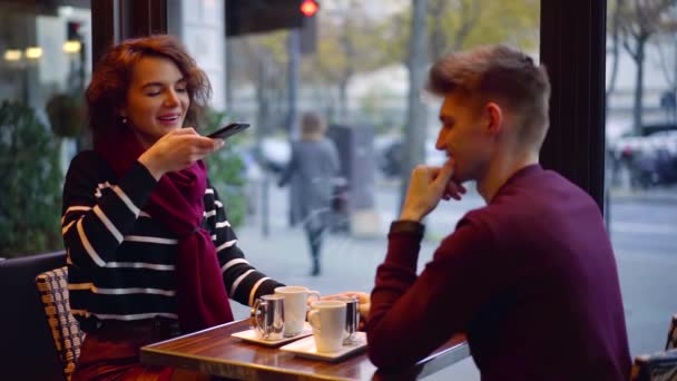 Two lovers sitting in cafe in chilly autumn day in Paris, girl taking photo of food for instagram on smartphone.