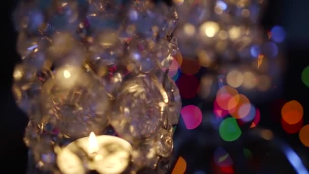 precious candleholder with flaming candles in darkness, moving and unfocused abstract shot, romantic and festive