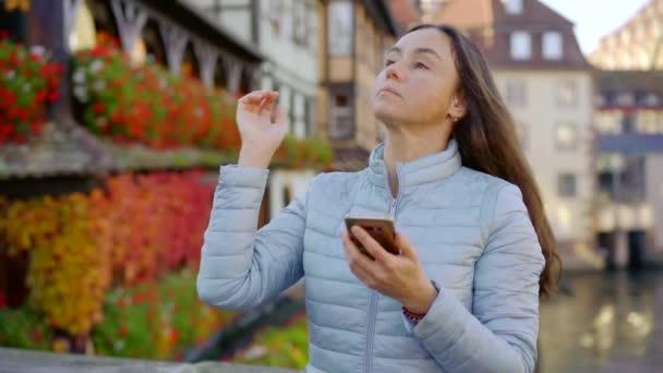 charmante Brünette tippt und sendet Nachrichten per Smartphone in einer kleinen Stadt mit Häusern im Hintergrund