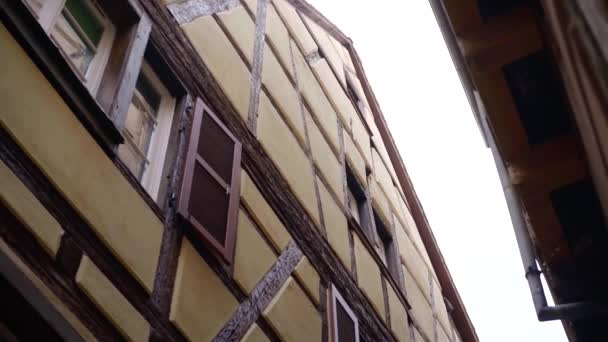 very narrow street between two half-timbered houses, tilt up view, moving shot, architecture