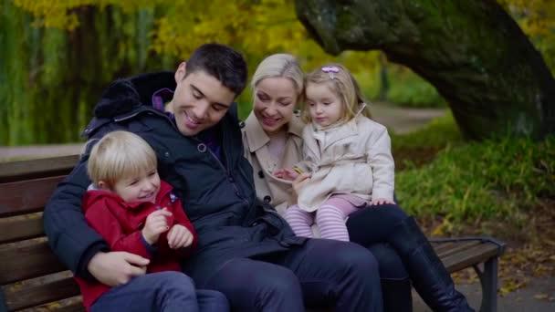 radostné rodiče s malými dětmi se odpočívá na lavičce v parku v podzimní den, baví