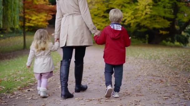 roztomilá holčička a kluk se drží za ruce matky procházky v parku v podzimní den, šlápnutí na cesty
