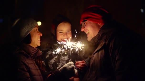 vidám család ünnepli Szilveszter, az utcán, a hideg. égő gyertya szikrázik a kezedben