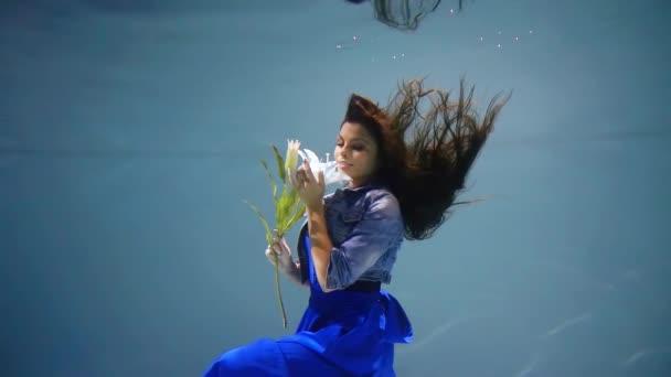 fiatal lány, egy kék ruhás víz alatt egy virág a kezében, mint a mesében