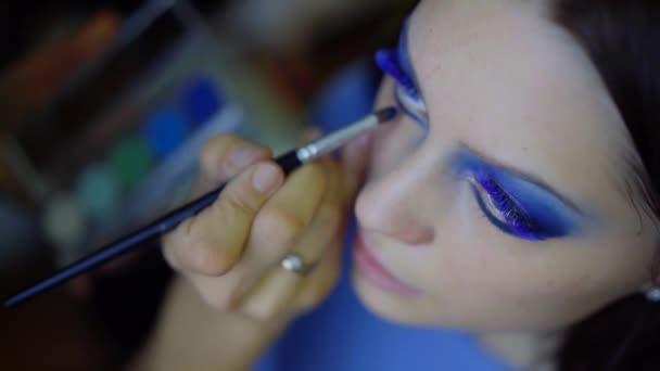 Chiuda in su. il volto di una giovane ragazza. mano guidata causa un colore vivido trucco per occhi azzurri con la bellezza delle sue ciglia