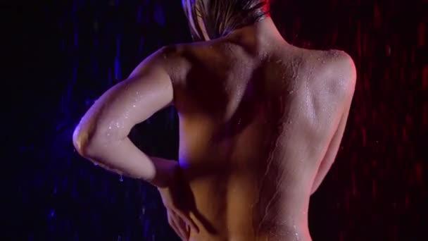 Rücken eines schlanken athletischen jungen Mädchens. Wäsche unter der Dusche in einem dunklen Raum im Licht von Neon-Rot und Blau
